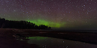 A view of the Northern Lights over the Lake Superior shoreline and reflections in a small pool of water during the spring melt. Marquette, MI