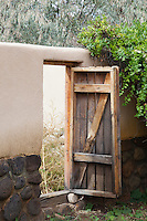 wooden door held open by a large rock in Abiquiu, New Mexico