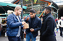 London, UK. 25.10.2014. three young men have their lunch form the food stalls at Borough Market, Southwark. Photograph © Jane Hobson.