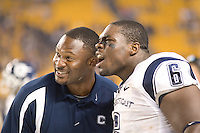 Connecticut Huskies defensive tackle Dan Davis and a Huskies coach watch a replay on the scoreboard of Lawrence Wilson's 51-yard interception return for a touchdown against the Pitt Panthers on September 22, 2007.  The Huskies beat the Panthers 34-14 at Heinz Field, Pittsburgh, Pennsylvania.