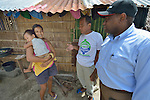John Nduna (right), the general secretary of the ACT Alliance, talks with Mercy Estosane, who is holding her 2-year old son Jay, in Bacubac, a neighborhood in Basey in the Philippines province of Samar that was hit hard by Typhoon Haiyan in November 2013. The storm was known locally as Yolanda. Translating for them is Efrain Ancaha, the neighborhood captain. The ACT Alliance has been providing a variety of forms of assistance to survivors here, and Nduna and other ACT Alliance leaders spent several days in affected communities learning first hand about the network's emergency response and long-term plans for recovery and rehabilitation.