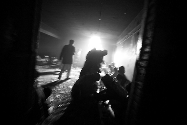 Light from the outside streams into a room full of opium and heroin addicts in the ruins of the former Soviet Cultural Center in Kabul, Afghanistan. More than 90 percent of the world's opium--from which heroin is derived--comes from Afghanistan, and its cheap availability is wreaking havoc on a society already ravaged by 30 years of war. As many as 2,000 addicts gather each day to get high inside in derelict building, which was almost completely destroyed during the 1992-1994 civil war. Feb. 2, 2009.