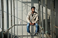 A migrant waits at the gate of the Athens Central Police Asylum Department, to apply for a visa or temporary resident status. Few applications are noticed; the department is notorious for being an administrative nightmare. According to UNHCR, 38,992 immigrants arrived in Greece in the first 10 months of 2010, whereas in 2009 the number was only 7,574.