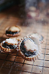 Some fresh mince pies on a cooling rack with icing sugar being sprinkled ontop.