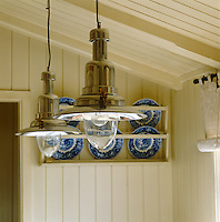 Detail of a pair of modern chrome pendant lanterns hanging over the dining room table in a Norwegian country cabin