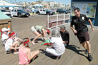 "Santa Monica Police Officer Jacob Holloway plays ""Duck, Duck, Goose"" with a group on a corporate retreat scavenger hunt at the Santa Monica Pier on Friday, July 1, 2011."