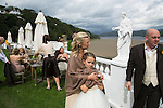 "Portmeirion, in North Wales, is a resort, where no one has ever lived. A self-taught Welsh architect named Sir Clough Williams-Ellis built it out of architectural salvage between the 1920s and 1970s, loosely based on his memories of trips to Portofino. Including a pagoda-shaped Chinoiserie gazebo, some Gothic obelisks, eucalyptus groves, a crenellated castle, a Mediterranean bell tower, a Jacobean town hall, and an Art Deco cylindrical watchtower. He kept improving Portmeirion until his death in 1978, age 94. It faces an estuary where at low tide one can walk across the sands and look out to sea. At high tide, the sea is lapping onto the shores. Every building in the village is either a shop, restaurant, hotel or self-catering accomodation. The village is booked out at high season, with numerous wedding receptions at the weekends. Very popular amongst the English and Welsh holidaymakers. Many who return to the same abode season after season. Hundreds of tourists visit every day, walking around the ornamental gardens, cobblestone paths, and shopping, eating ice-creams, or walking along the woodland and coastal paths, amongst a colourful assortment of hydrangea, rhododendrons, tree ferns and redwoods. The resort boasts two high class hotels, a la carte menus, a swimming pool, a lifesize concrete boat, topiary, pools and wishing wells. The creator describes the resort as ""a home for fallen buildings,"" and its ragged skyline and playful narrow passageways which were meant to provide ""more fun for more people."" It does just that.///A wedding reception taking place in the grounds of Portmeirion Hotel, the estuary behind."