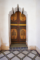 Berber Arabesque painted wood door and Zellige tile floor.The Petite Court, Bahia Palace, Marrakesh, Morroco