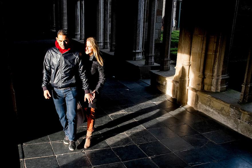 Nederland, Utrecht, 23 feb 2014<br /> Stel loopt een lichtstraal in in een donkere kloostergang. <br /> <br /> Foto(c): Michiel Wijnbergh
