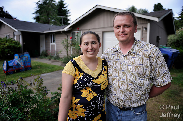 Larisa and Veaceslav Cosoi, immigrants from Moldova, in the front yard of their Tacoma, Washington, house. The couple came to the United States in 2006 with three children, assisted by Lutheran Immigration Services. They were helped locally by Tacoma Community House, a mission institution of United  Methodist Women.