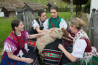 Girls in traditional folk dresses pet a sheep during the Easter celebration in the Skansen open air ethnographic museum in Szenna (about 200 km South-West of capital city Budapest), Hungary on April 14, 2017. ATTILA VOLGYI