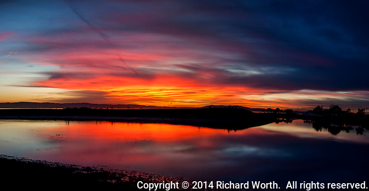 The sky over San Francisco Bay glows in warm shades of orange at sunset.  San Leandro Marina Park, San Leandro, California.