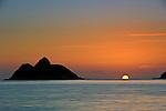 Fireball emerges from horizon between Mokulua Islands at Lanikai Beach