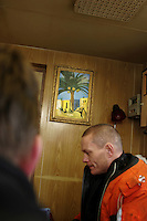 Coastguard inspector onboard russian freight ship Murminsk while she is loading fish from fishing trawler Topaz A, just off Bjørnøya. Fishing inspector Jarl Inge Nielsen sits below a painting with a scene very distant from the Arctic waters they are in. Coastguard vessel KV Svalbard patrols the northermost waters of Norway, including around the islands that she is named after. The main task is inspecting fishing boats, but she also performs search and rescue missions, and environmental monitoring.
