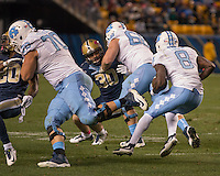 North Carolina linemen Caleb Peterson (70) and Lucas Crawley (68) block for running back TJ Logan (8) as Ptt defenders Jevonte Pitts (20) and Mike Caprara (30) try to defend. The North Carolina Tar Heels football team defeated the Pitt Panthers 26-19 on Thursday, October 29, 2015 at Heinz Field, Pittsburgh, Pennsylvania.