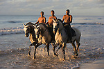 Three vaqueros ride their Lusitano horses on the beach in Bahia, Brazil.