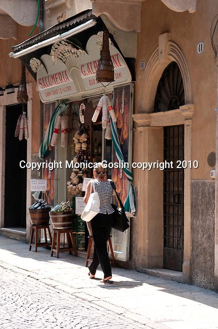 A woman walks by a deli in Verona, Italy.