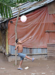 A boy plays with a balloon on the La Lempira Cooperative, near Ceibita, Honduras. La Lempira is an agricultural project which has been seized by armed peasants who claim the land is rightfully theirs under the country's agrarian reform law.