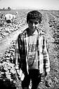 Turquie 1998.Un jeune kurde ramassant des légumes avec sa famille prés d'Izmir. .Turkey 1998.Young Kurdish boy picking up vegetables in a field near Izmir
