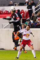 Nick DeLeon (18) of D. C. United heads the ball over Connor Lade (16) of the New York Red Bulls. D. C. United defeated the New York Red Bulls 1-0 (2-1 in aggregate) during the second leg of the MLS Eastern Conference Semifinals at Red Bull Arena in Harrison, NJ, on November 8, 2012.
