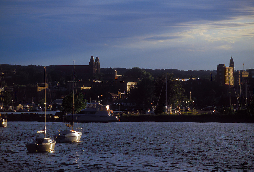 Sailboats ar seen in the lower harbor of Marquette, Mich as late afternoon sun breaks through the clouds.