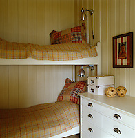 This small bedroom has bunk beds with checked bed covers and cushions