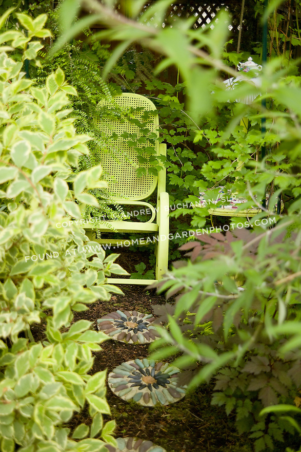 a yellow painted metal rocker sits tucked among ferns and lush foliage in this garden vignette in a backyard residentail garden