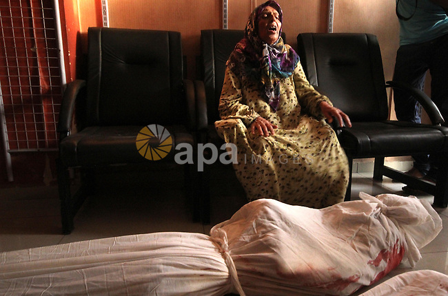 A Syrian woman mourns over the body of a relative following an air strike by government forces on the al-Mowasalat neighbourhood of the northern Syrian city of Aleppo on September 20, 2015. Photo by Ameer al-Halbi
