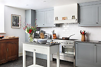 The basement kitchen is furnished with a wall of contemporary built-in cupboards and an antique cabinet