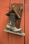 Old cowboy boot hanging on the side of a red barn