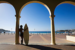 A surfer stands in the shade of the historic Pavilion at Bondi Beach.  Sydney, New South Wales, AUSTRALIA.