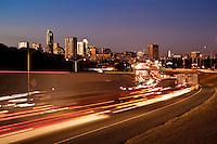 Sunset falls on the Austin Skyline as I-35 Rush Hour Traffic flows through downtown Austin, Texas.