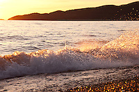 A wave breaks in the sunset light on the shores of Canada's inland sea, Lake Superior Provincial Park.