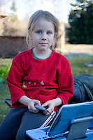Kid Girl Playing Laptop Computer in Yard
