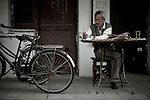 A man practices calligraphy on the street in Yangzhou, China, a suburb city of Shanghai and major producer of photovoltaic cells for solar power.