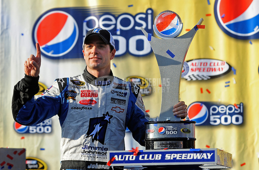 Oct. 11, 2009; Fontana, CA, USA; NASCAR Sprint Cup Series driver Jimmie Johnson celebrates after winning the Pepsi 500 at Auto Club Speedway. Mandatory Credit: Mark J. Rebilas-