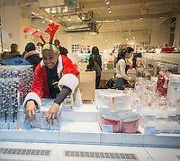 A worker dressed as a reindeer adjusts stock in the window of a store in New York on Wednesday, December 23, 2015. (© Richard B. Levine)