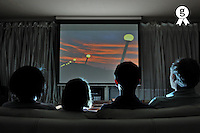 Family watching movie at home on projection screen (Licence this image exclusively with Getty: http://www.gettyimages.com/detail/103810540 )