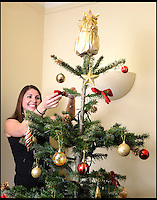 BNPS.co.uk (01202) 558833<br /> Picture: LauraJones/BNPS<br /> <br /> Receptionist at Humphries Kirk solicitors and arbitrators in Dorchester, Dorset Gemma Wall decorating their Christmas tree they rent each year.<br /> <br /> En-tree-preneur Peter Inch has found an innovative way to stop Christmas trees being discarded after the festive season - by renting and replanting them.<br /> <br /> The businessman has grown around 3,000 pine trees on his farm that he charges people to use in their homes during the holiday period.<br /> <br /> Peter delivers the trees to customers' doors at the end of November and then collects them in the first week of January.<br /> <br /> Once he has picked up the trees they are placed back in the ground in tubs and linked up to a watering system that revives them after being inside for so long.