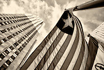 In sepia, Liberian flag seen flying to right of 30 Rockefeller Center, GE Building, seen from low angle, at Rockefeller Plaza, Manhattan, New York City, USA, on January 24, 2012. The nation of Liberia, which is a member state of the United Nations, has official flag with one white star on a blue square background in upper corner, and total of 11 horizontal stripes, alternating in color: 6 red stripes and 5 white stripes.