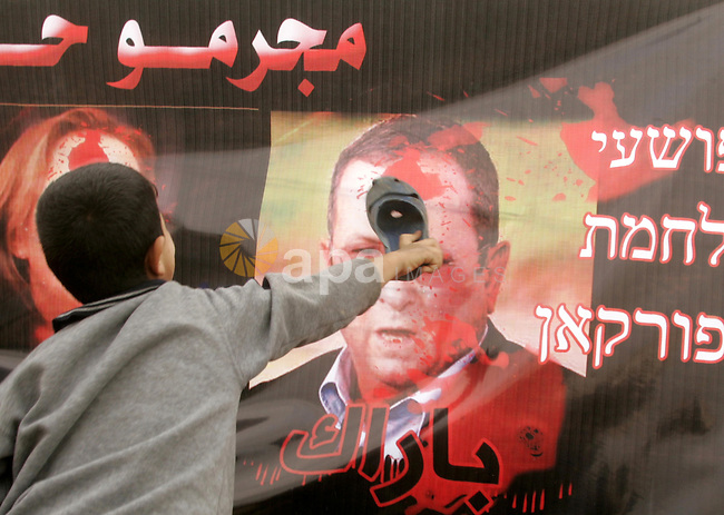 Palestinian child throws shoes at a poster depicting the blood-smeared faces of Israeli Defence Minister Ehud Barak during a protest near the Rafah border with Egypt on December 31, 2009 against the underground barrier Egypt is building along its border with the Gaza Strip. Egypt has only implicitly confirmed the construction of the underground wall, which was first reported by Israeli media, saying it is aimed at shutting down the extensive network of smuggling tunnels along the border. Photo by Abed Rahim Khatib