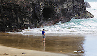 A hiker looks at rough surf by a sea cave at Hanakapi'ai Beach, reached by the Kalalau Trail, Kaua'i.