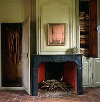 A classical fireplace and French boiserie typify the restoration style of many of the rooms in this chateau
