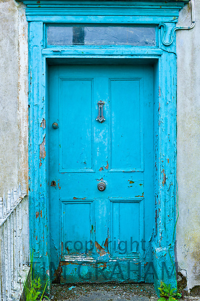 Brightly painted weathered doorway of quayside house in Courtmacsherry, County Cork, Ireland