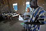 Sister Ninet D'Costa, FMA, a Catholic nun from India, is a teacher trainer in Malakal, Southern Sudan. Sister D'Costa came to the war-torn African country under the auspices of Solidarity with Southern Sudan, an international network of Catholic groups supporting Southern Sudan with educational personnel and prayer. Here Sister D'Costa supervises teacher Simon Amum's work in a classroom in Detang, a small village across the Upper Nile River from Malakal. NOTE: In July 2011 Southern Sudan became the independent country of South Sudan.