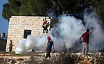 Palestinian protesters hurl stones at Israeli security forces during a protest against the expansion of the nearby Jewish settlement of Halamish, in the West Bank village of Nabi Saleh near Ramallah, Friday, Nov. 30, 2012. Photo by Issam Rimawi