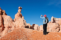 Female hiker takes photo of Hoodoo formations from Queens Garden trail, Bryce Canyon national park, Utah, USA