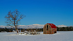 Washington, Northeast, Elk. A barn with red roof with distant snow covered mountains.