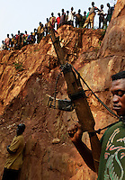 A security guard waves a fake gun that is a symbol of authority to guard the gold mine. Most Africans in the Congo work where the Belgians already explored.  Congolese try to eke little bits of gold from the old mine tunnels and cracks in the earth left by the Belgians. Belgians moved very quickly into their colony with heavy machinery to extract gold to finance the war effort during WWII.