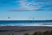 Kitesurfers on a Northumberland (Northeast of England beach). Despite the cold waters, many kitesurfing enthusiasts come to these extensive beaches to make use of the contant wind, essential for kitesurfing.